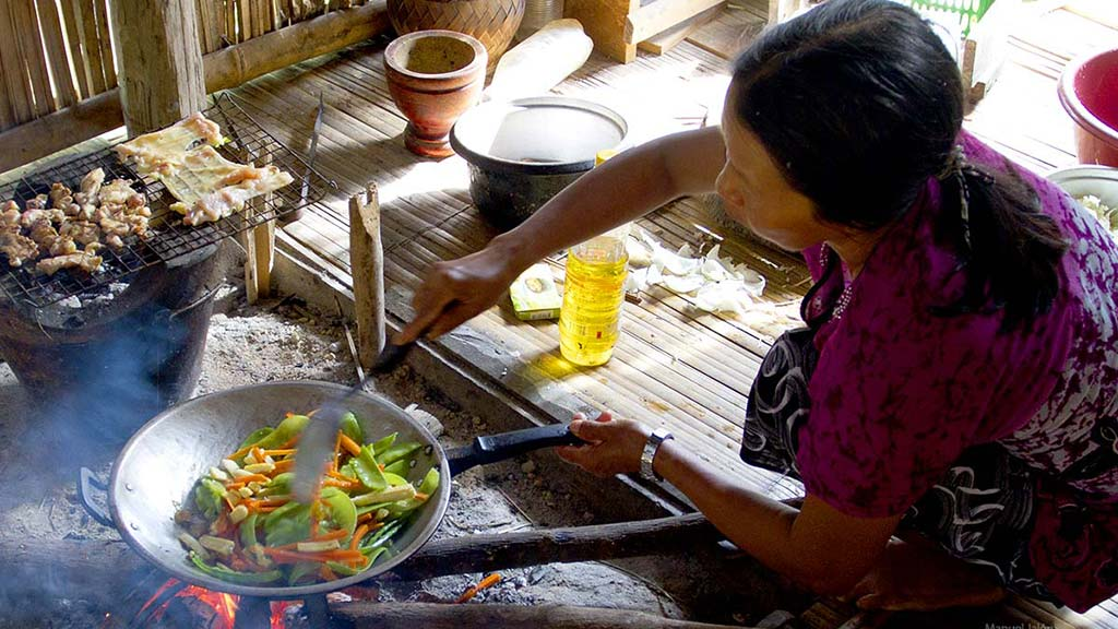 Akha mother cooking in the kitchen.