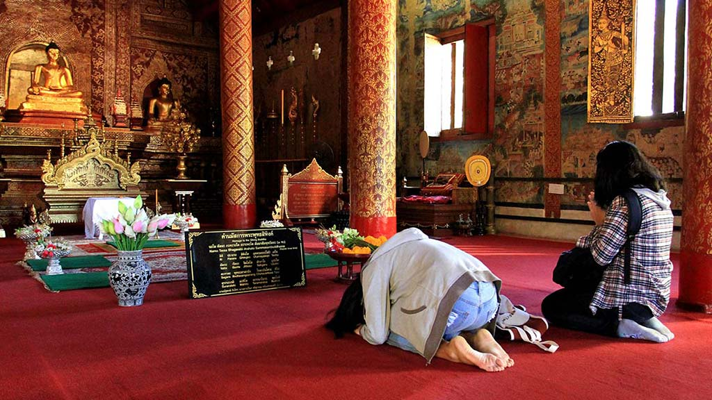 Girls praying in a temple, Wat Phra Singh, Chiang Mai.